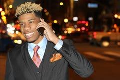 Χαμογελώντας αφρικανικός επιχειρηματίας που καλεί τηλεφωνικώς στην οδό τη νύχτα - εικόνα αποθεμάτων Στοκ εικόνα με δικαίωμα ελεύθερης χρήσης
