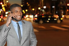 Χαμογελώντας αφρικανικός επιχειρηματίας που καλεί τηλεφωνικώς στην οδό τη νύχτα - εικόνα αποθεμάτων Στοκ Φωτογραφίες