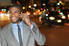 Χαμογελώντας αφρικανικός επιχειρηματίας που καλεί τηλεφωνικώς στην οδό τη νύχτα - εικόνα αποθεμάτων Στοκ Φωτογραφία