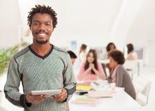 Χαμογελώντας αφρικανικός φοιτητής πανεπιστημίου με μια ταμπλέτα στοκ εικόνα