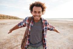 Χαμογελώντας αφρικανικό άτομο με τις αγκάλες που διαδίδονται που ανοίγουν στην παραλία Στοκ φωτογραφίες με δικαίωμα ελεύθερης χρήσης