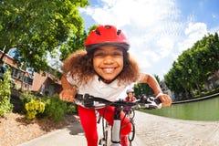 Χαμογελώντας αφρικανικό κορίτσι που οδηγά το ποδήλατό της το καλοκαίρι στοκ φωτογραφία