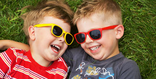 Χαμογελώντας αδελφοί που φορούν τα φανταχτερά γυαλιά ηλίου Στοκ Φωτογραφία