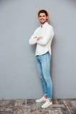 Χαμογελώντας βέβαιος νεαρός άνδρας στο καπέλο που στέκεται με τα χέρια που διπλώνονται Στοκ φωτογραφία με δικαίωμα ελεύθερης χρήσης