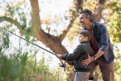 Χαμογελώντας βοηθώντας γιος πατέρων αλιεύοντας στο δάσος Στοκ φωτογραφίες με δικαίωμα ελεύθερης χρήσης
