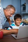 Χαμογελώντας βοηθώντας εγγονός παππούδων που χρησιμοποιεί το lap-top Στοκ φωτογραφία με δικαίωμα ελεύθερης χρήσης