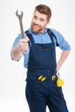 Χαμογελώντας γενειοφόρος νεαρός άνδρας που στέκεται και που παρουσιάζει γαλλικό κλειδί Στοκ φωτογραφίες με δικαίωμα ελεύθερης χρήσης