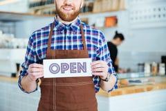 Χαμογελώντας γενειοφόρος σερβιτόρος στην καφετιά ποδιά που παρουσιάζει ανοικτό σημάδι Στοκ Φωτογραφίες