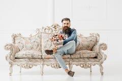 Χαμογελώντας γενειοφόρο άτομο με τα λουλούδια Στοκ εικόνες με δικαίωμα ελεύθερης χρήσης
