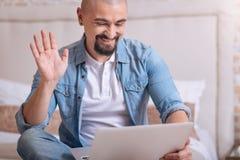 Χαμογελώντας γενειοφόρο άτομο που έχει τη συνομιλία μέσω του Διαδικτύου στοκ φωτογραφίες με δικαίωμα ελεύθερης χρήσης