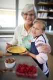 Χαμογελώντας γιαγιά και εγγονή που θέτουν κατασκευάζοντας την πίτα στοκ εικόνα