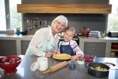 Χαμογελώντας γιαγιά και εγγονή που θέτουν κατασκευάζοντας την πίτα στοκ φωτογραφίες με δικαίωμα ελεύθερης χρήσης