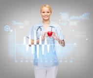 Χαμογελώντας γιατρός ή νοσοκόμα θηλυκών με την καρδιά Στοκ Εικόνα