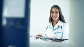 Χαμογελώντας γιατρός γυναικών που παίρνει το φάκελλο στο νοσοκομείο φιλμ μικρού μήκους