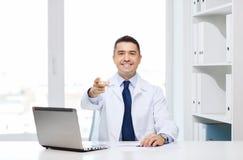 Χαμογελώντας γιατρός που δείχνει το δάχτυλο σε σας στην αρχή Στοκ Εικόνες