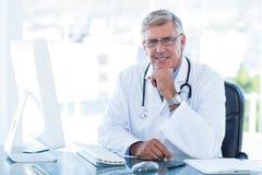 Χαμογελώντας γιατρός που εργάζεται στον υπολογιστή στο γραφείο του Στοκ εικόνα με δικαίωμα ελεύθερης χρήσης