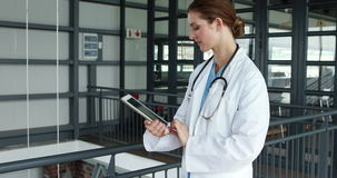 Χαμογελώντας γιατρός που χρησιμοποιεί την ταμπλέτα απόθεμα βίντεο