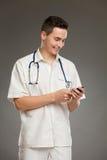 Χαμογελώντας γιατρός που χρησιμοποιεί το κινητό τηλέφωνο Στοκ Φωτογραφία
