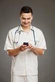 Χαμογελώντας γιατρός που χρησιμοποιεί το κινητό τηλέφωνο Στοκ Εικόνα