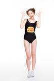 Χαμογελώντας γοητευτικό θηλυκό στο swimsut με το χάμπουργκερ που παρουσιάζει εντάξει σημάδι Στοκ Εικόνες