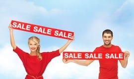 Χαμογελώντας γυναίκα και άνδρας με τα κόκκινα σημάδια πώλησης Στοκ Εικόνες