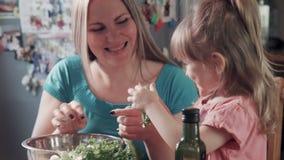 Χαμογελώντας γυναίκα και κορίτσι που προετοιμάζουν τη σαλάτα απόθεμα βίντεο