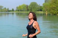Χαμογελώντας γυναίκα κοστουμιών λουσίματος στη λίμνη Στοκ Φωτογραφία