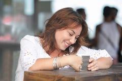 Χαμογελώντας γυναίκα με ένα φλυτζάνι του ποτού Στοκ φωτογραφίες με δικαίωμα ελεύθερης χρήσης