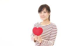 Χαμογελώντας γυναίκα με μια κόκκινη καρδιά Στοκ Εικόνες