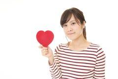 Χαμογελώντας γυναίκα με μια κόκκινη καρδιά Στοκ εικόνες με δικαίωμα ελεύθερης χρήσης