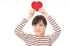 Χαμογελώντας γυναίκα με μια κόκκινη καρδιά Στοκ φωτογραφία με δικαίωμα ελεύθερης χρήσης