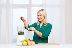 Χαμογελώντας γυναίκα με τα μαγειρεύοντας τρόφιμα μπλέντερ στο σπίτι στοκ εικόνες