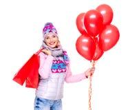 Χαμογελώντας γυναίκα με τα δώρα και τα κόκκινα μπαλόνια μετά από να ψωνίσει Στοκ Φωτογραφίες