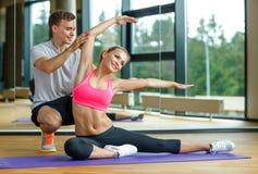 Χαμογελώντας γυναίκα με την αρσενική άσκηση εκπαιδευτών στη γυμναστική Στοκ φωτογραφίες με δικαίωμα ελεύθερης χρήσης