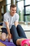 Χαμογελώντας γυναίκα με την αρσενική άσκηση εκπαιδευτών στη γυμναστική Στοκ εικόνες με δικαίωμα ελεύθερης χρήσης
