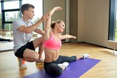 Χαμογελώντας γυναίκα με την αρσενική άσκηση εκπαιδευτών στη γυμναστική Στοκ Φωτογραφία