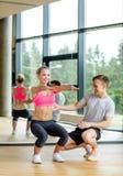 Χαμογελώντας γυναίκα με την αρσενική άσκηση εκπαιδευτών στη γυμναστική Στοκ Εικόνες