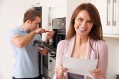Χαμογελώντας γυναίκα με την επισκευή Μπιλ Στοκ Εικόνα