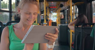 Χαμογελώντας γυναίκα με την ταμπλέτα στο λεωφορείο απόθεμα βίντεο