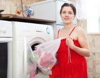 Χαμογελώντας γυναίκα με την τσάντα πλυντηρίων στην κουζίνα στοκ εικόνα με δικαίωμα ελεύθερης χρήσης
