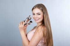 Χαμογελώντας γυναίκα με τις βούρτσες makeup Στοκ Εικόνες
