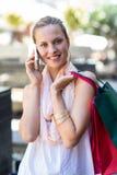 Χαμογελώντας γυναίκα με τις τσάντες αγορών που καλούν με το κινητό τηλέφωνο Στοκ Εικόνες