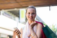 Χαμογελώντας γυναίκα με τις τσάντες αγορών που καλούν με το κινητό τηλέφωνο Στοκ εικόνες με δικαίωμα ελεύθερης χρήσης