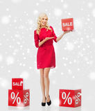 Χαμογελώντας γυναίκα με το κόκκινο σημάδι πώλησης πέρα από το χιόνι Στοκ εικόνα με δικαίωμα ελεύθερης χρήσης