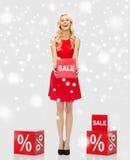Χαμογελώντας γυναίκα με το κόκκινο σημάδι πώλησης πέρα από το χιόνι Στοκ εικόνες με δικαίωμα ελεύθερης χρήσης