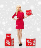 Χαμογελώντας γυναίκα με το κόκκινο σημάδι πώλησης πέρα από το χιόνι Στοκ Φωτογραφία
