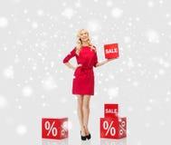 Χαμογελώντας γυναίκα με το κόκκινο σημάδι πώλησης πέρα από το χιόνι Στοκ Εικόνα