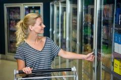 Χαμογελώντας γυναίκα με το ψυγείο ανοίγματος κάρρων Στοκ Φωτογραφία
