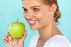 Χαμογελώντας γυναίκα με το όμορφο χαμόγελο, λευκιά εκμετάλλευση Apple δοντιών Στοκ εικόνα με δικαίωμα ελεύθερης χρήσης
