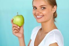 Χαμογελώντας γυναίκα με το όμορφο χαμόγελο, λευκιά εκμετάλλευση Apple δοντιών Στοκ φωτογραφία με δικαίωμα ελεύθερης χρήσης
